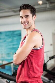 Hombre sonriente con los brazos cruzados en el gimnasio