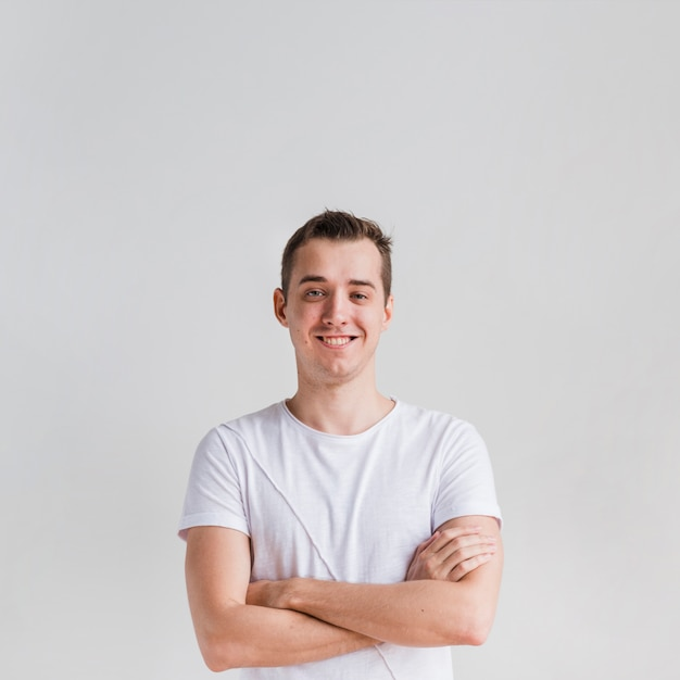 Hombre sonriente con los brazos cruzados mirando a cámara