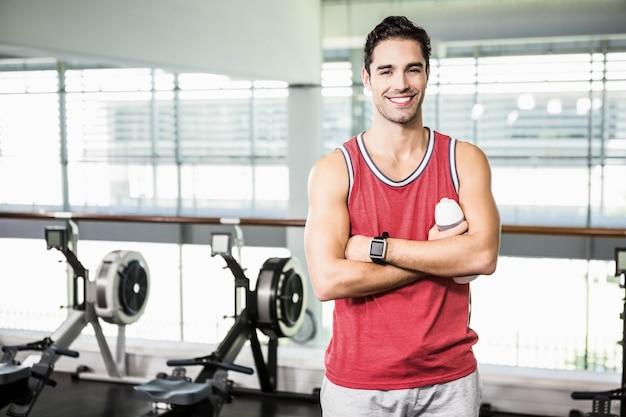 Hombre sonriente con los brazos cruzados sosteniendo una botella de agua en el gimnasio