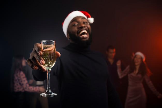 Hombre sonriente brindando con champán para año nuevo