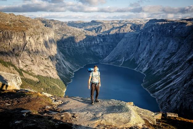 Un hombre sonriente camina por las montañas con una mochila.