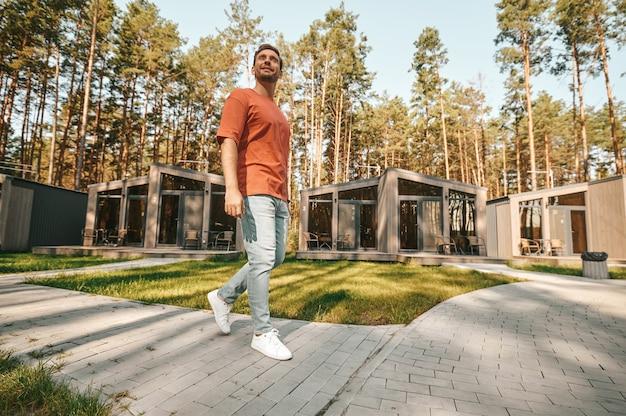 Hombre sonriente caminando en el área de recreación de la naturaleza