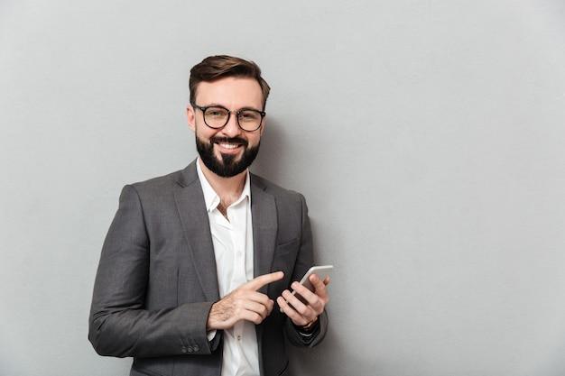 Hombre sonriente en camisa blanca escribiendo mensajes de texto o desplazamiento de alimentación en la red social con teléfono inteligente sobre gris