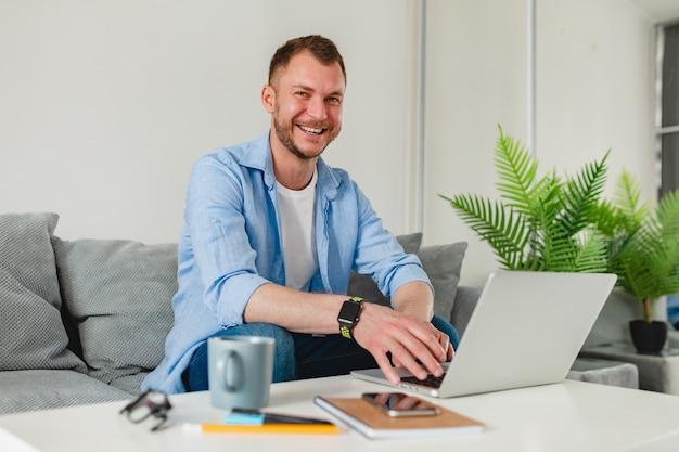 Hombre sonriente en camisa sentado relajado en el sofá en casa en la mesa trabajando en línea en la computadora portátil desde casa
