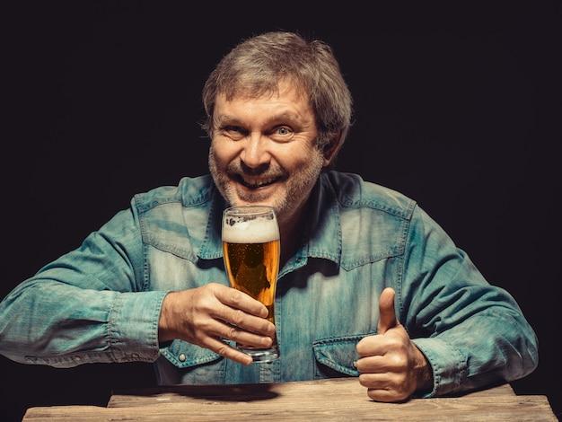 Hombre sonriente en camisa vaquera con vaso de cerveza