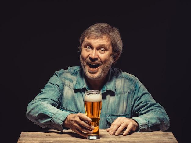 El hombre sonriente en camisa vaquera con vaso de cerveza