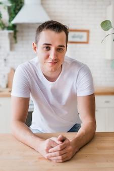 Hombre sonriente en la camiseta blanca que se sienta en la cocina