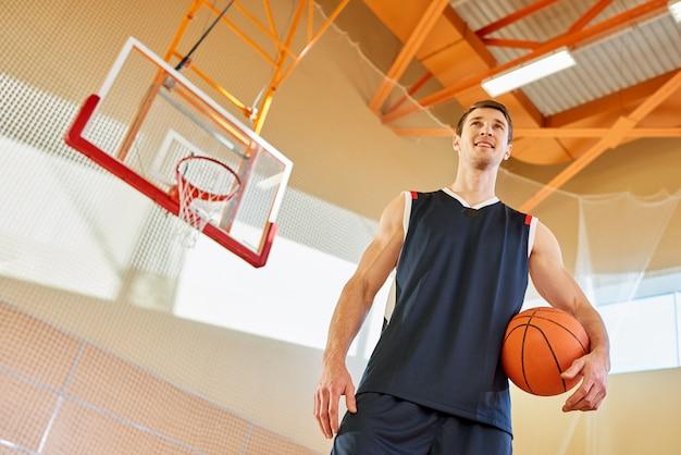 Hombre sonriente en la cancha de básquet