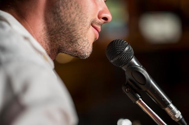 Hombre sonriente cantando en el micrófono en una barra borrosa