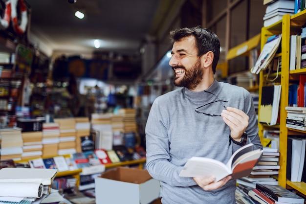 Hombre sonriente caucásico hermoso que se coloca en librería con el libro en manos y que mira lejos.