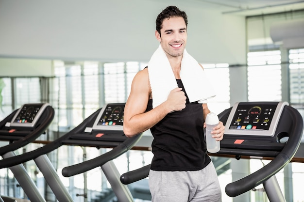 Hombre sonriente en cinta rodante con botella de agua en el gimnasio