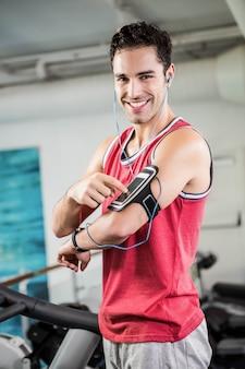 Hombre sonriente en la cinta con teléfono inteligente en el gimnasio