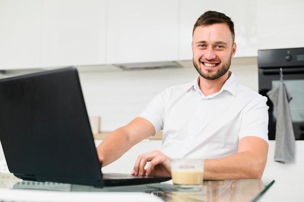 Hombre sonriente en cocina con laptop en frente