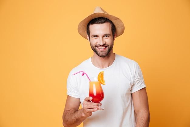 Hombre sonriente con cóctel mirando a cámara