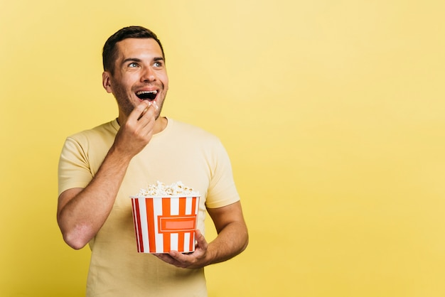 Hombre sonriente comiendo palomitas de maíz con espacio de copia