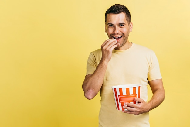 Hombre sonriente comiendo palomitas de maíz