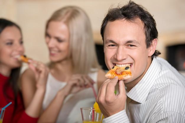 El hombre sonriente está comiendo una pizza. dos chicas están hablando.