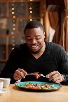 Hombre sonriente comiendo en el restaurante