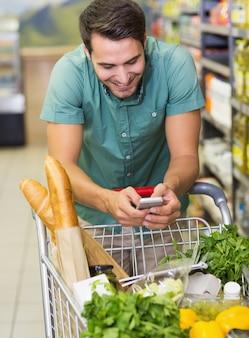 Hombre sonriente compra productos y usa su smaprtphone