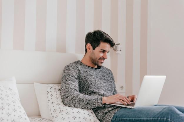 Hombre sonriente con la computadora portátil en la cama