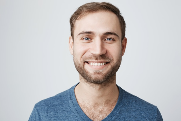 Hombre sonriente contento con barba mirando a cámara