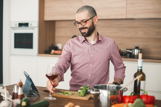 Hombre sonriente con copa de vino cocinando guiso de verduras con tableta. está cortando brócoli, calabacín, pimiento rojo, cebolla y otras verduras.