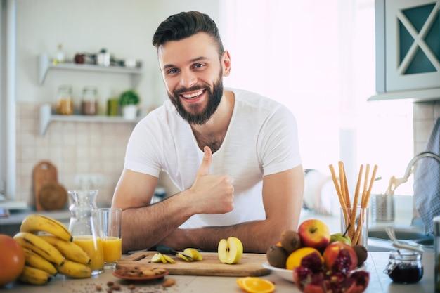 Hombre sonriente deportivo joven hermoso en la cocina con frutas. concepto de alimentación saludable