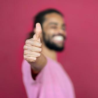 Hombre sonriente desenfocado haciendo el signo similar