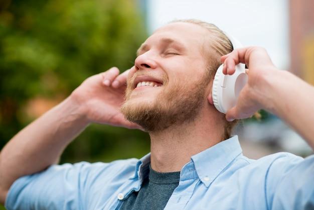 Hombre sonriente disfrutando de música en auriculares