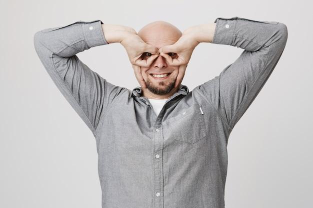 Hombre sonriente divertido mostrar máscara de superhéroe con los dedos