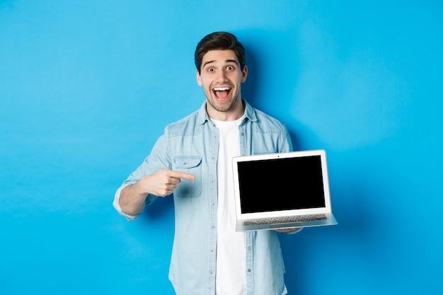 Hombre sonriente emocionado apuntando a la pantalla del portátil