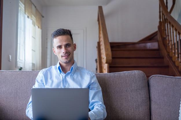 Hombre sonriente emocionado mirando a la cámara, usando la aplicación de computadora portátil, escribiendo un mensaje en la red social, leyendo noticias, correo electrónico, estudiante chateando trabajando, jugando, viendo videos divertidos