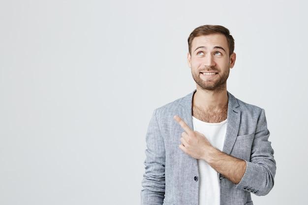 Hombre sonriente emocionado que señala en la esquina superior izquierda del anuncio