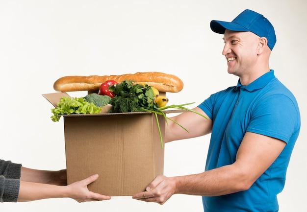Hombre sonriente entregando caja de cartón con comida
