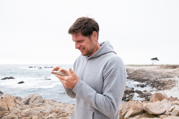 Hombre sonriente enviando mensajes de texto sobre fondo asombroso de la naturaleza