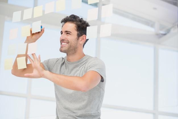 Hombre sonriente escribiendo en notas adhesivas en la ventana