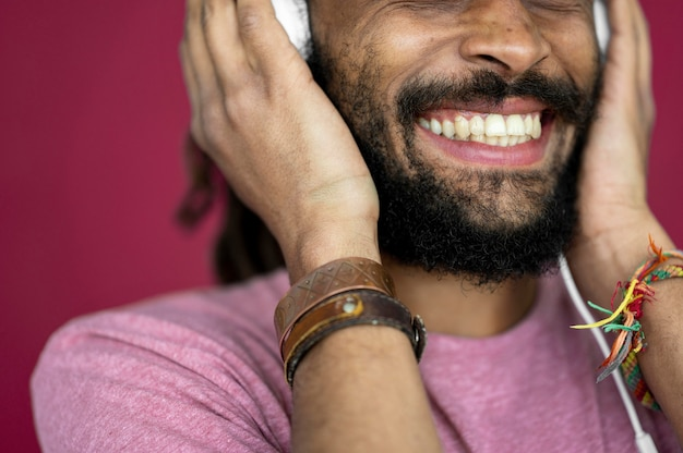 Hombre sonriente escuchando música a través de auriculares