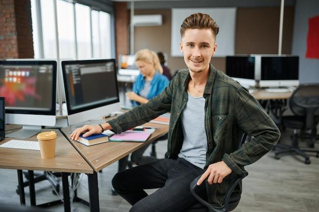 Hombre sonriente especialista en ti se sienta a la mesa en la oficina. programador web o diseñador en el lugar de trabajo, ocupación creativa. tecnología de la información moderna, equipo corporativo.
