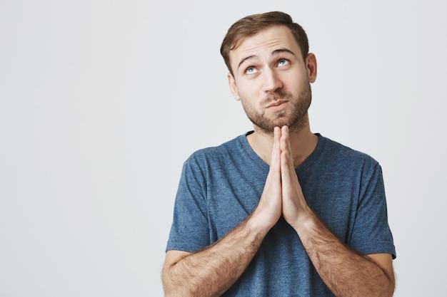 Hombre sonriente esperanzado pidiendo deseo, rezando a dios