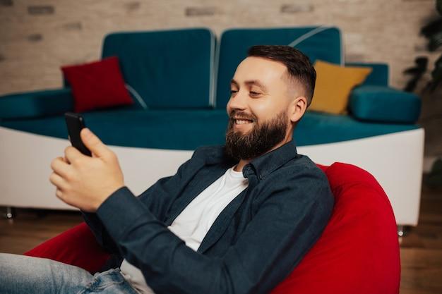 Hombre sonriente feliz descansa en un sillón en la sala de estar y mira videos divertidos en el teléfono inteligente.