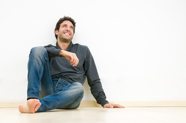 Hombre sonriente feliz mirando hacia arriba y soñando con su futuro