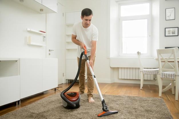 Hombre sonriente feliz que limpia la alfombra