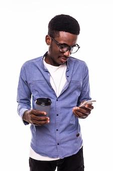 Hombre sonriente feliz del retrato del primer que lee buenas noticias en el teléfono elegante que sostiene la pared blanca aislada móvil, de consumición de la taza de café. expresión de rostro humano, emoción, ejecutivo corporativo