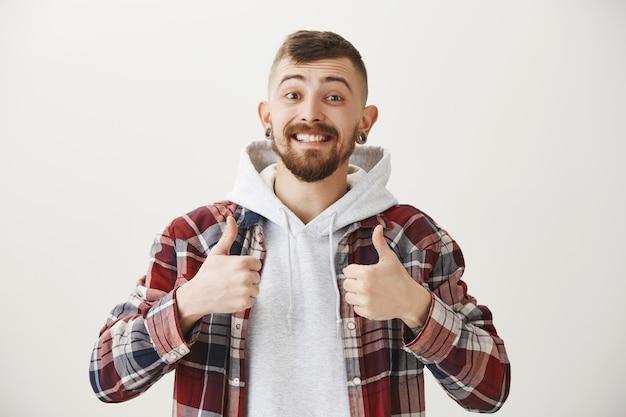 Hombre sonriente feliz solidario mostrando el pulgar hacia arriba, alabando el buen trabajo, bien hecho