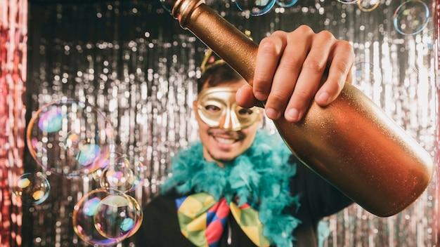 Hombre sonriente en fiesta de carnaval con botella de champagne