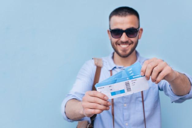 Hombre sonriente con gafas de sol mostrando boleto aéreo sobre fondo azul.