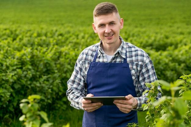 Hombre sonriente en la granja con tableta