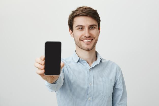 Hombre sonriente guapo mostrando la pantalla del teléfono inteligente
