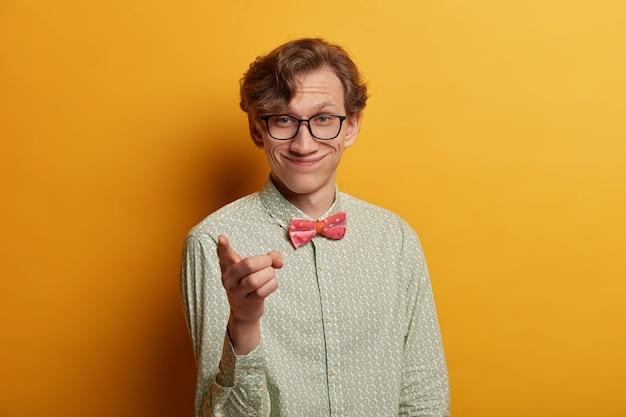 El hombre sonriente guapo positivo le indica, señala con el dedo índice directamente, usa una camisa de moda, elige a alguien, usa gafas, posa sobre una pared amarilla. deberías unirte a mi