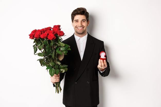 Hombre sonriente guapo en traje negro, sosteniendo rosas y anillo de compromiso